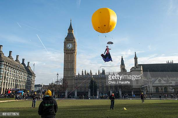 Greenpeace activists float a picture of Mary Poppins wearing a gas mask in front of the Houses of Parliament to highlight that London has breached...
