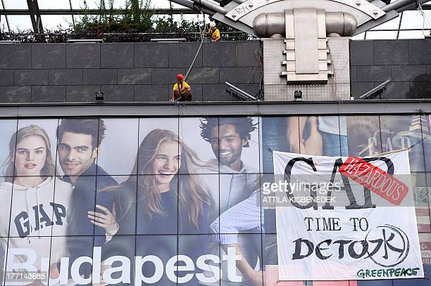 Greenpeace activists hang a banner which reads 'GAP hazardous time to detox' to protest at an advertisement of GAP clothes shop in Budapest on August...