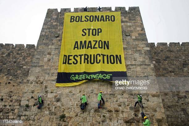 Greenpeace activists hang a large banner on the ramparts of the Old City of Jerusalem with a message to the visiting Brazilian president concerning...
