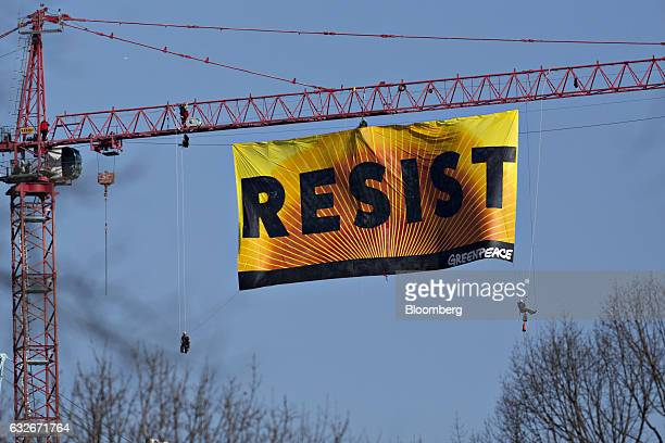 Greenpeace activists hang from a construction crane with a banner that reads Resist in Washington DC US on Wednesday Jan 25 2017 The protest comes...