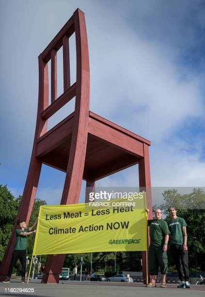 Greenpeace activists hold a banner reading 'less meat : less heat, climate action now', during a protest prior to the publication by The UN's...
