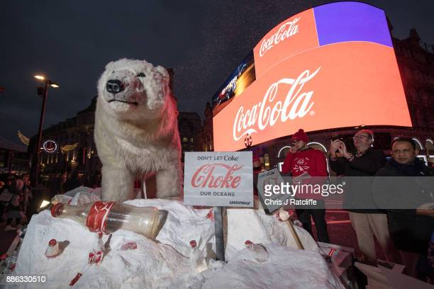 Greenpeace activists hold a demonstration in front of the Piccadilly Circus electronic billboard as part of a global campaign to get Coca Cola to...