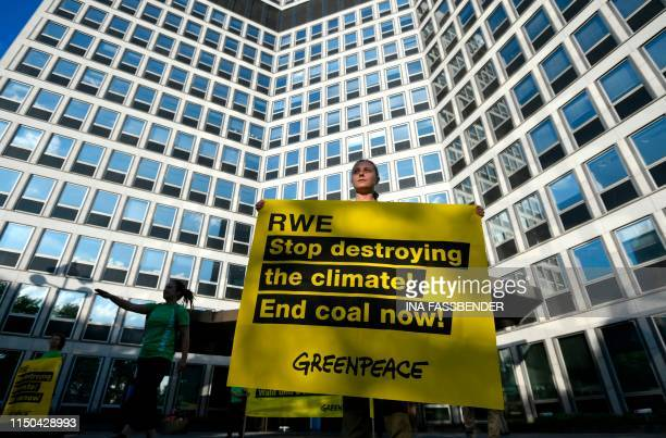 Greenpeace activists hold banners outside the German utility company RWE's HQ on June 18 2019 in Essen western Germany during a protest against coal...