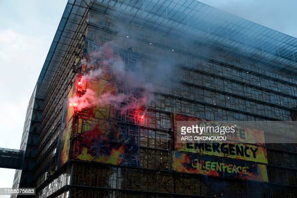 Greenpeace activists hold flares after hanging a banner on the building of the European Council in Brussels on December 12, 2019 during an action of...