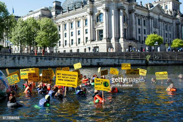Greenpeace activists hold placards as they swim in the river Spree by the Reichstag building to campaign for more climate protection in Berlin,...