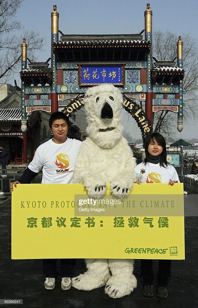 Greenpeace activists hold up a sign supporting the Kyoto protocol on February 16, 2005 in Beijing, China. Greenpeace offices around the world celebrate the coming into force of the protocol today. After more than ten years of protracted negotiations, thirty five industrialised countries along with the European Community are now legally bound to reduce or limit their greenhouse gas emissions.