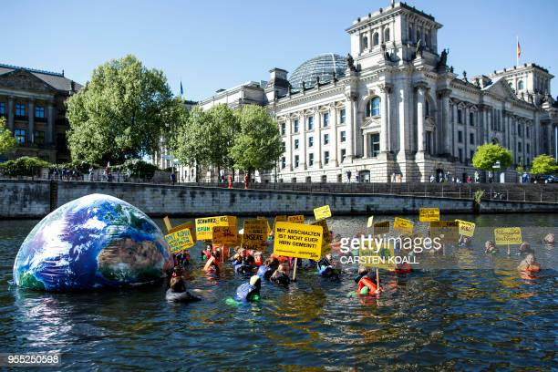 Greenpeace activists hold up posters as they swim with an inflatable globe through the river Spree past the Reichstag building housing the Bundestag...