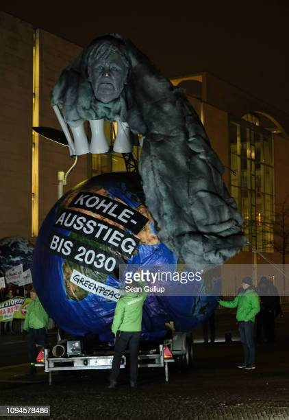 Greenpeace activists inflate a Planet Earth balloon and an effigy of German Chancellor Angela Merkel spewing CO2 prior to a meeting between Merkel...