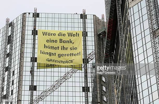 Greenpeace activists install a twelve by thirteen meters large banner that reads 'Waere die Welt eine Bank haettet ihr sie laengst gerettet...