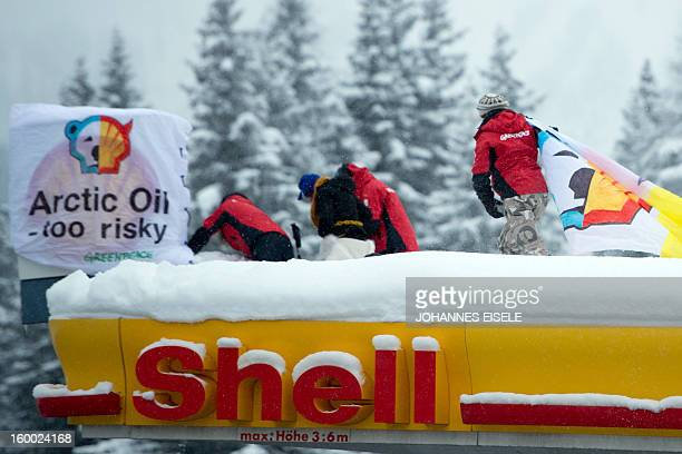 Greenpeace activists install banner on the roof of a filling station during a protest against global oil giant Shell on January 25 2013 in Wolfgang...