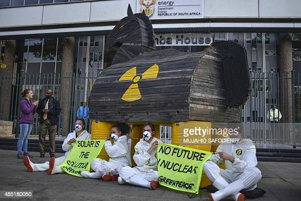 Greenpeace activists locked themselves to a mock Trojan horse they built and chained to the front gate of the South African Department of Energy's...