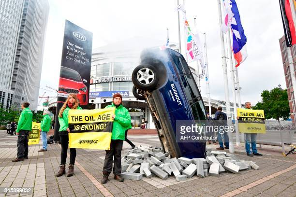 Greenpeace activists protest against climatedamaging cars with an installation with a car setup upright and banners reading 'the oil age is ending'...