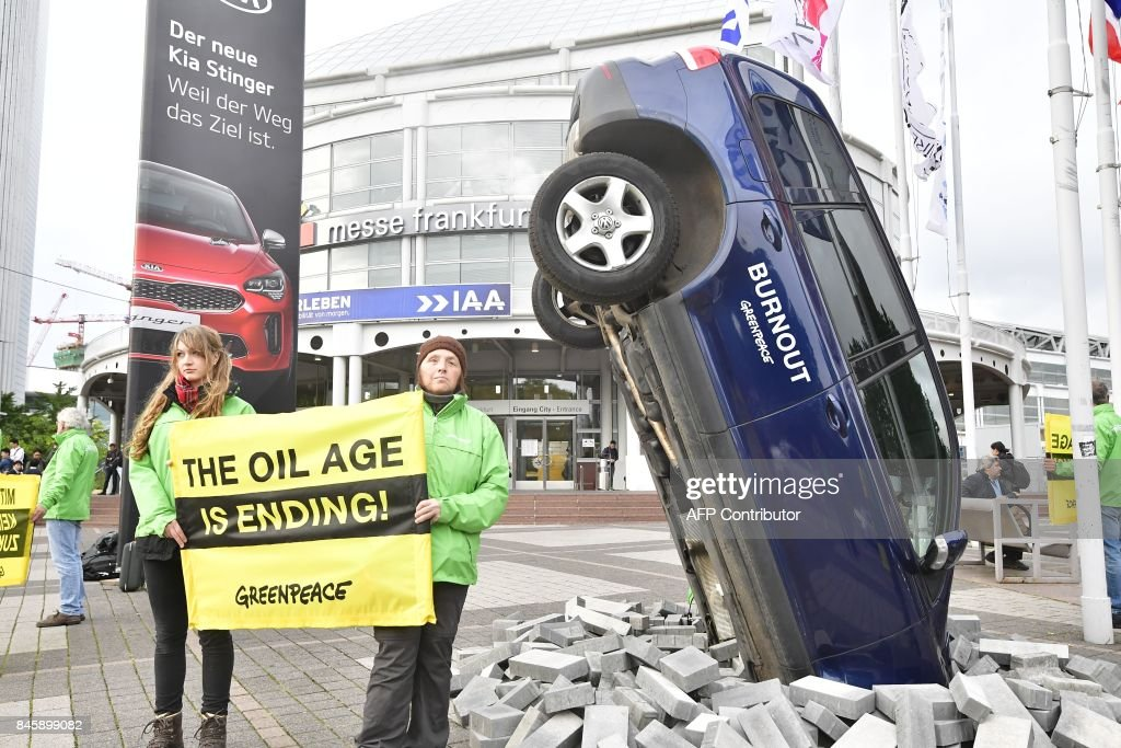 Greenpeace activists protest against climate-damaging cars with an installation with a car set-up upright and banners reading 'the oil age is ending' on the sidelines of the Frankfurt Motor Show IAA in Frankfurt am Main, western Germany, on September 12, 2017. According to organisers, around 1,000 exhibitors from 39 countries will showcase their products and services. This year's fair running from September 14 to 24, 2017 will focus on digitization, urban mobility and electric mobility. / AFP PHOTO / Tobias SCHWARZ