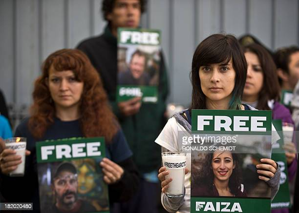 Greenpeace activists protest on September 27 2013 in front of the Russian embassy in Mexico City with signs calling for the release of activists from...