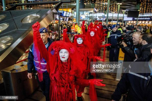 Greenpeace activists protest to denounce airline pollution in the main hall of the Amsterdam Schiphol airport on December 14, 2019. / Netherlands OUT...