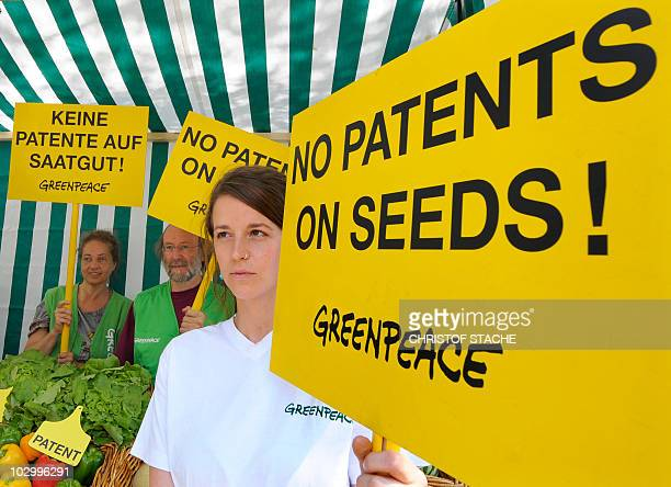 Greenpeace activists protest with placards reading 'No patents on seeds' next to a stand with vegetables during a demonstration against food patents...