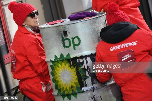 Greenpeace activists sit chained into oil barrels as they protest outside the headquarters of oil giant BP in London on February 5 on the day that...