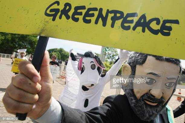 Greenpeace activists stand a demonstration in front of the government palace in Brasilia October 13 2009 demanding President Luiz Inacio Lula da...