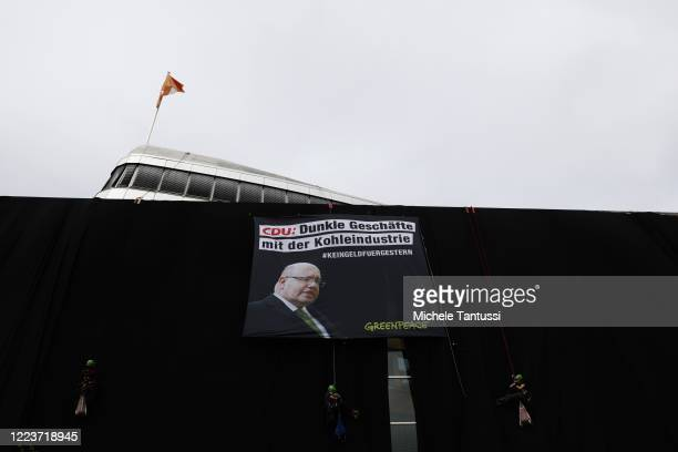 Greenpeace activists suspended on ropes cover the CDU Headquarters Konrad Adenauer Haus with Black fabric and a Banner showing the Economy and Energy...