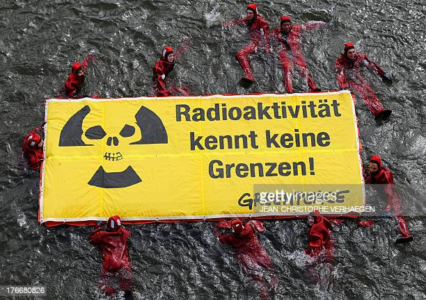 Greenpeace activists swimming in the river Moselle hold a banner reading 'Radioactivity has no borders' as they demonstrate on August 17 2013 in...