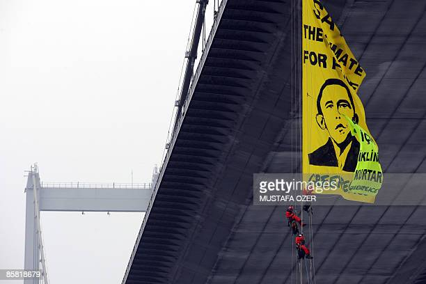 Greenpeace activists unfurl a banner bearing an image of US president Barak Obama and a slogan which translates as Save the climate for peaceas they...