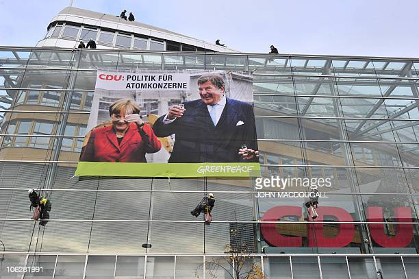 Greenpeace activists unfurl a giant banner featuring German Chancellor Angela Merkel toasting with energy giant RWE CEO Juergen Grossmann at the...