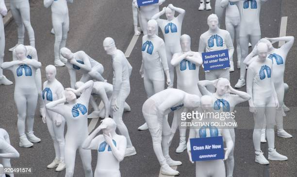 Greenpeace activists wear white morphsuits with lungs painted on them and hold a poster reading 'We have the right to clean air' as they stage an...