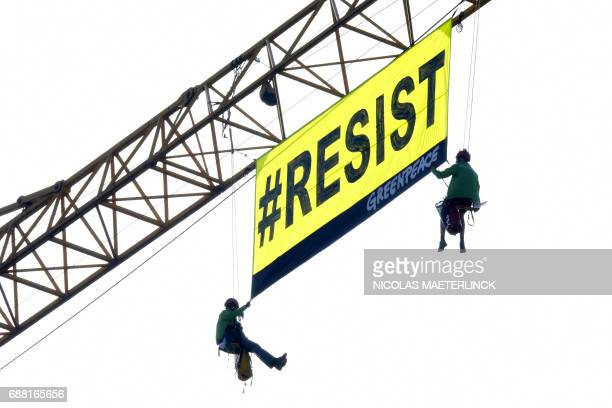 Greenpeace activits unfurl a banner reading 'Resist' from atop a construction crane to protest against the President of The United States of America...