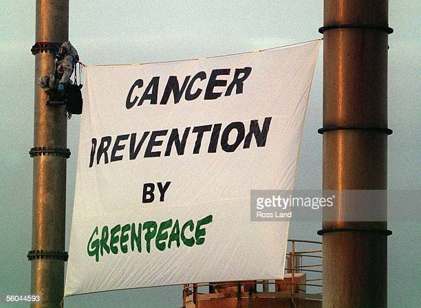 Greenpeace protester in chemical protection gear hangs from a chimney stack at the Medical Waste Ltd plant in Allens rd East Tamaki