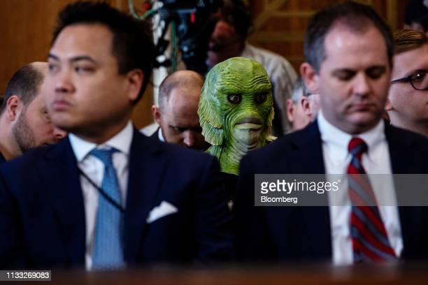 A Greenpeace protester wearing a mask listens during a confirmation hearing for David Bernhardt US secretary of interior nominee for US President...