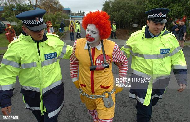 Greenpeace protestor Gareth Hughes dressed like Ronald McDonald is removed and arrested by police after attaching himself to the gates of the fast...