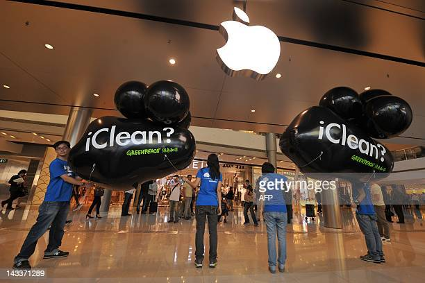 Greenpeace protestors holding black plastic balloons resembling black clouds stand at the entrance of the Apple store in Hong Kong on April 25 2012...
