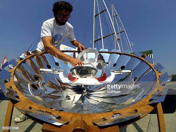 Greenpeace Rainbow Warrior ship crew member shows how to use the solar energy and a big mirror to cook a soup at the Black sea port of Varna, Friday,...