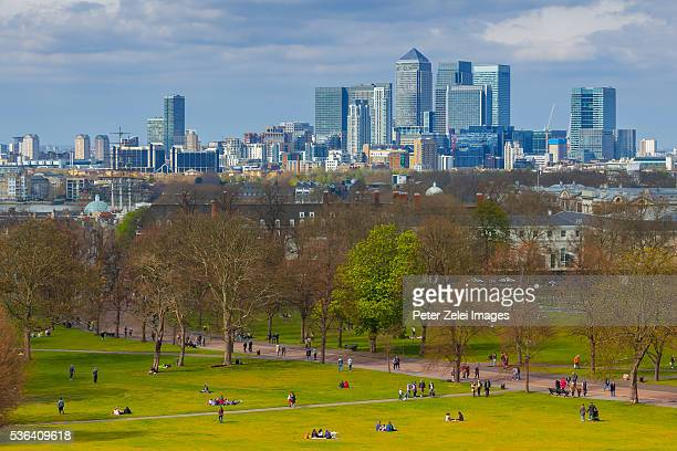 greenwich park in london with the skyscrapers of canary wharf in the background - greenwich london stock pictures, royalty-free photos & images