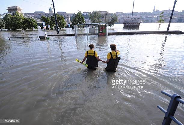 Greepeace activists walk in the flooded water of River Danube at the Chain Bridge of Budapest downtown to protest for the climate change on June 9,...