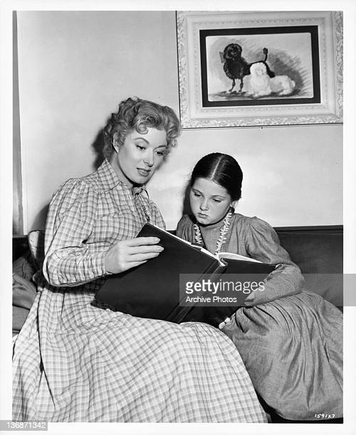 Greer Carson and Donna Corcoran sit reading a book together in a scene from the film 'Scandal At Scourie' 1952