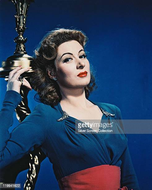 Greer Garson British actress wearing a blueandred outfit poses in a studio portrait against a blue background circa 1945