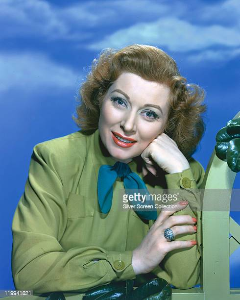 Greer Garson British actress wearing a green blouse with a blue bow with her head resting on her hand in a studio portrait against a background of...