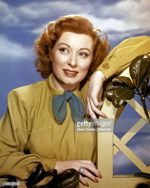 Greer Garson British actress wearing a yellow blouse with a green bow in a studio portrait against a background of blue sky and clouds circa 1945