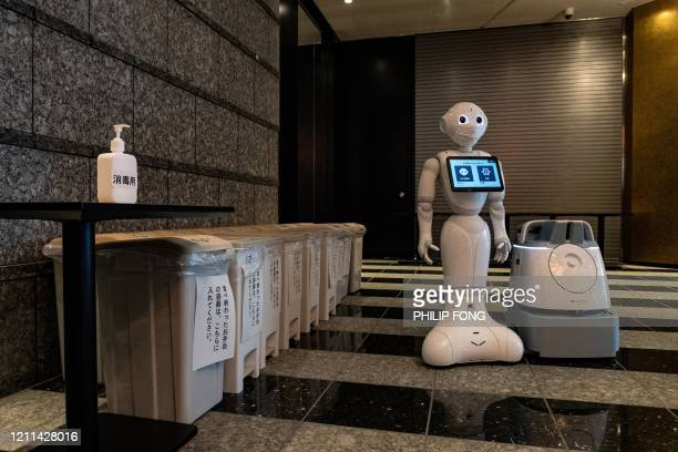 TOPSHOT A greeting robot called Pepper and a cleaning robot called Whiz stand in the lobby of a hotel during the first day the building is used as a...