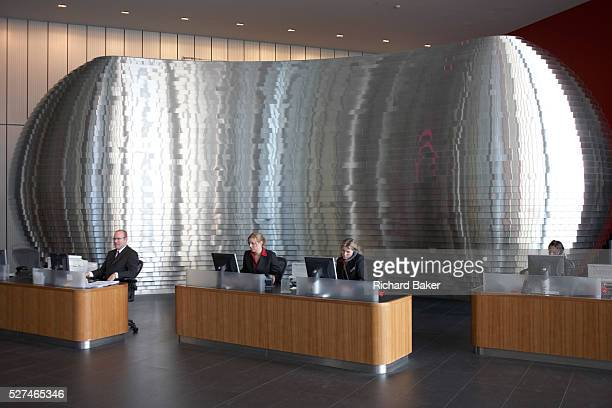 Greeting visitors to Ernst Young's Norman Fosterdesigned 385000 square foot European headquarter are a team of receptionists seated working at PC...