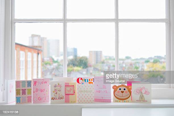 Greetings cards for new baby girl on windowsill