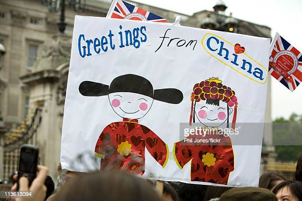 "Greetings from China"" banner is lifted high above the crowds outside the gates of Buckingham Palace during the Royal Wedding of Prince William to..."