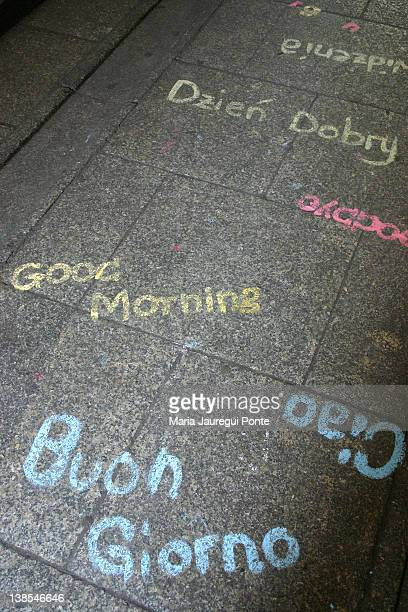 Greetings written in various languages on a sidewalk