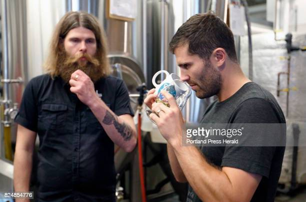 Greg Abbot right sniffs a mug of heather and a glass of hops while determining the appropriate ratio for a smallbatch beer he brewed with Stulli...