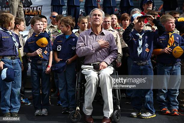 Greg Abbott a candidate for governor is seen on stage with Cub Scouts during the national anthem prior to the NASCAR Sprint Cup Series AAA Texas 500...