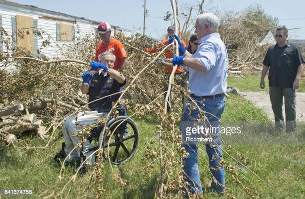 Greg Abbott governor of Texas left and US Vice President Mike Pence second right clear tree limbs during a trip to survey the damage from Hurricane...