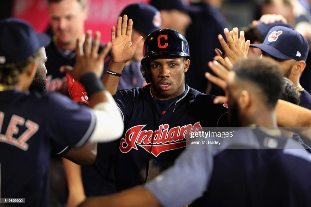 Greg Allen #53 is congratulated in the dugout after scoring on an RBI single hit by Austin Jackson #26 of the Cleveland Indians during the ninth inning of a game against the Los Angeles Angels of Anaheim at Angel Stadium of Anaheim on September 19, 2017 in Anaheim, California.