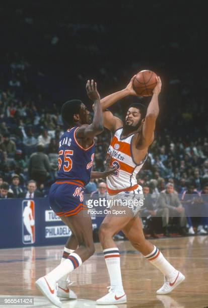 Greg Ballard of the Washington Bullets looks to pass the ball over the top of Albert King of the New Jersey Nets during an NBA basketball game circa...