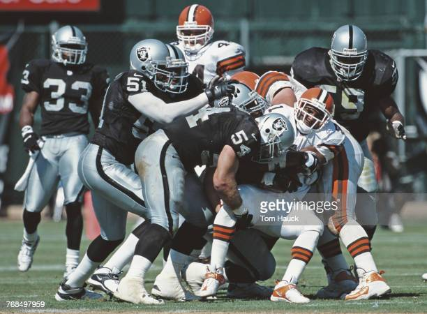 Greg Biekert and Lance Johnstone of the Oakland Raiders tackles Travis Prentice Running Back for the Cleveland Browns during their National Football...